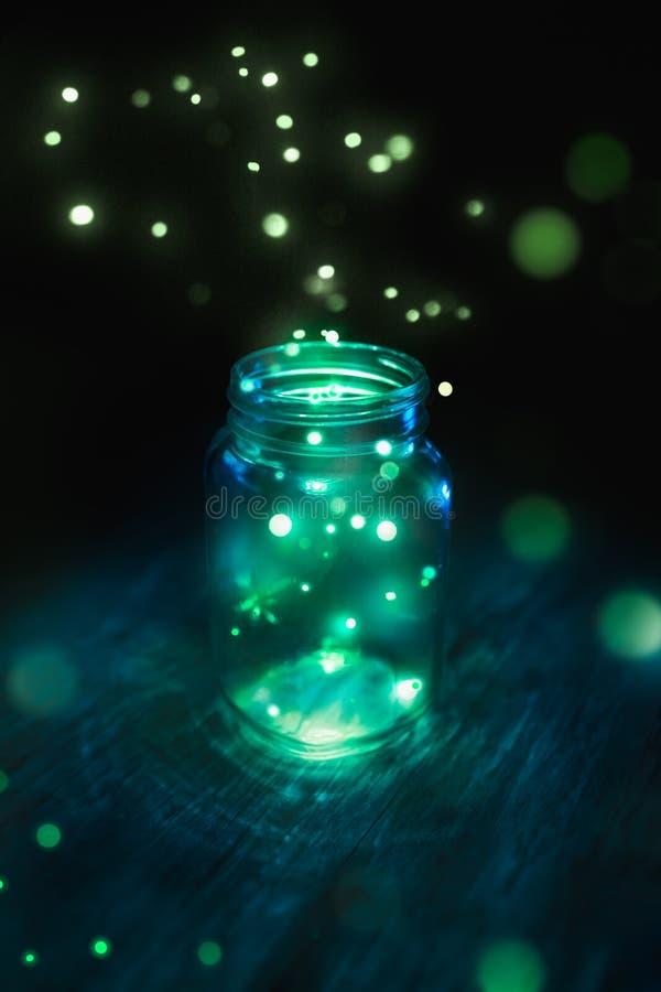 在一个瓶子的萤火虫在黑暗的背景 免版税图库摄影