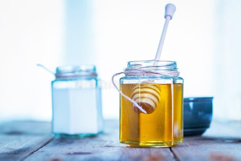 在一个瓶子的蜂蜜用后边酸奶 免版税库存照片