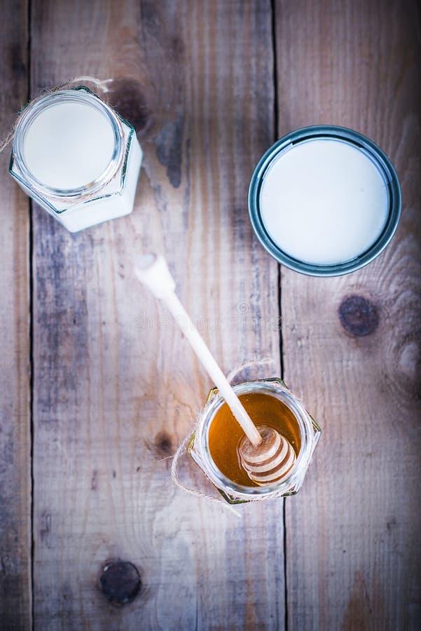 在一个瓶子的蜂蜜用在旁边酸奶 免版税库存照片