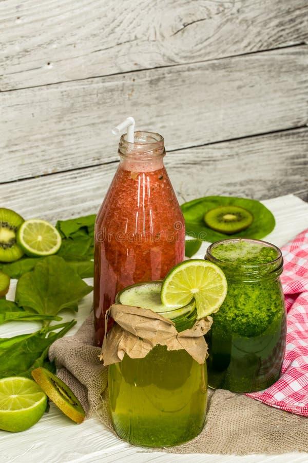 在一个瓶子的绿色和红色圆滑的人有石灰的,猕猴桃 图库摄影