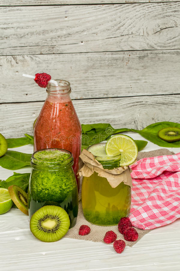在一个瓶子的绿色和红色圆滑的人有石灰的,猕猴桃 免版税库存照片