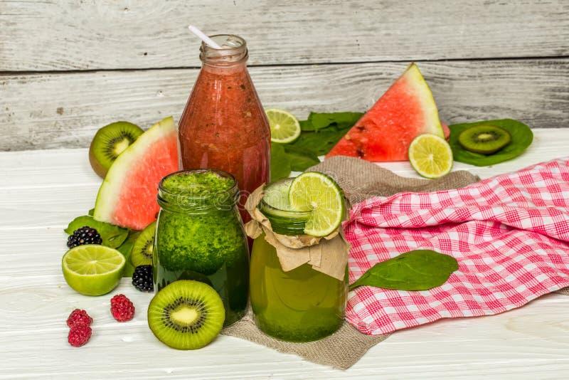 在一个瓶子的绿色和红色圆滑的人有石灰的,猕猴桃 免版税图库摄影
