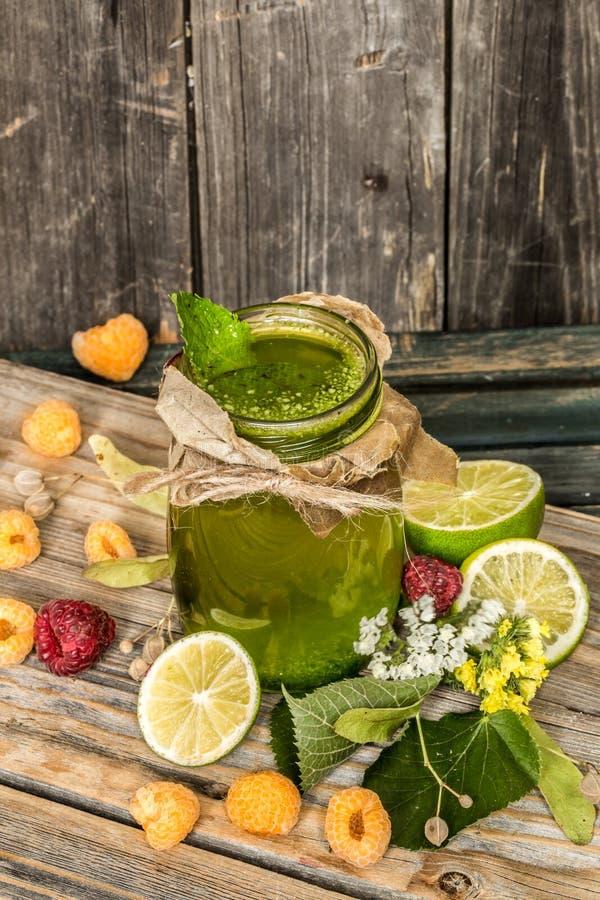 在一个瓶子的绿色圆滑的人有石灰、猕猴桃和莓果的 库存图片