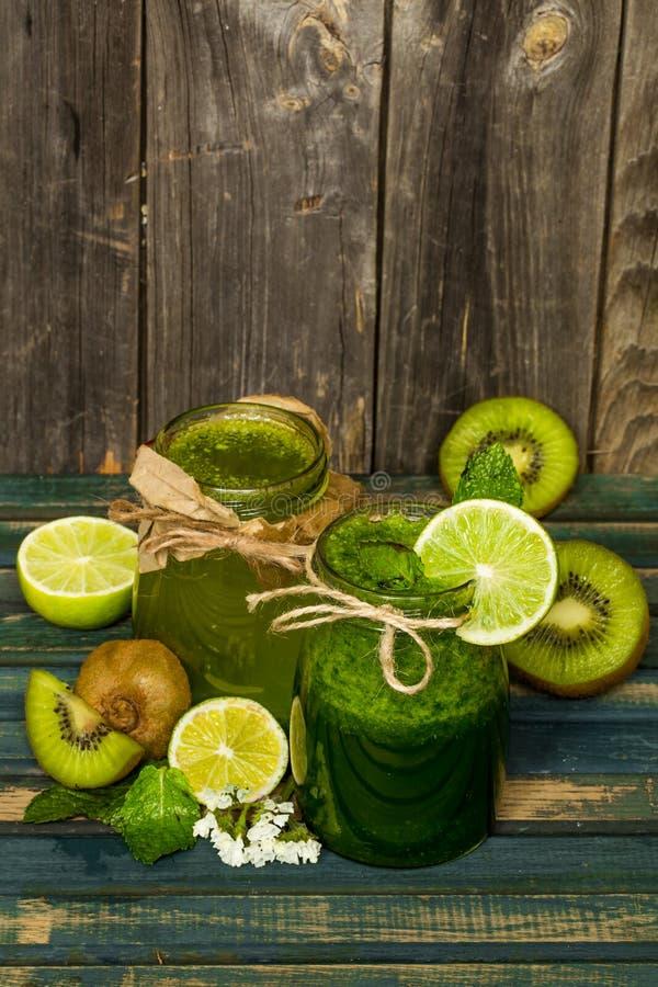 在一个瓶子的绿色圆滑的人有石灰、猕猴桃和莓果的 免版税库存图片