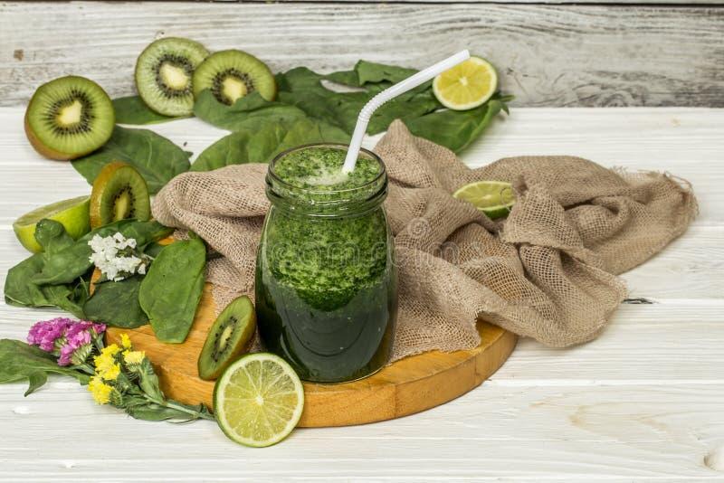 在一个瓶子的绿色圆滑的人有石灰和莓果的 图库摄影