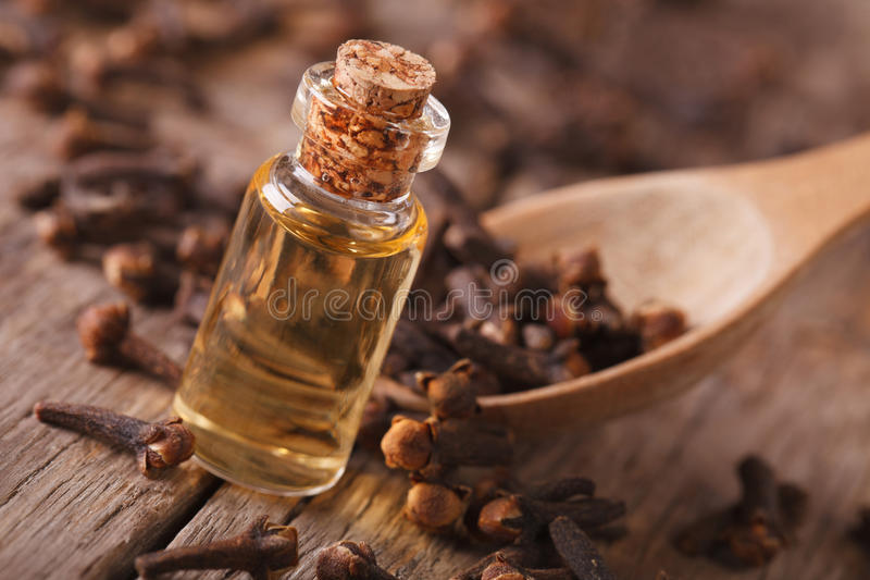 在一个瓶特写镜头的丁香油在桌上,土气 免版税库存照片
