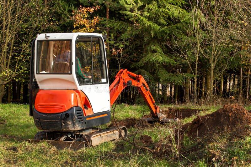在一个生态房子的建造场所工作 挖掘机调整地形 一位小挖掘者在庭院里 免版税库存照片