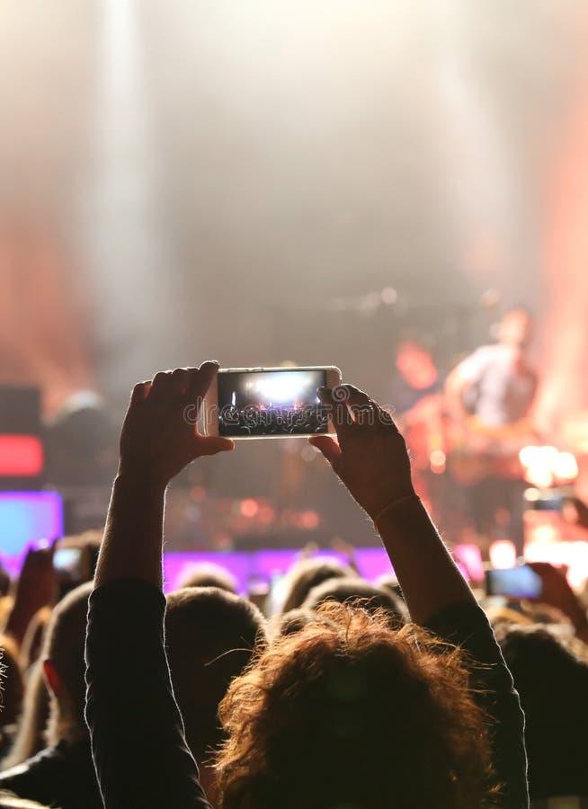 在一个生活音乐会期间,女孩拍照片 库存图片