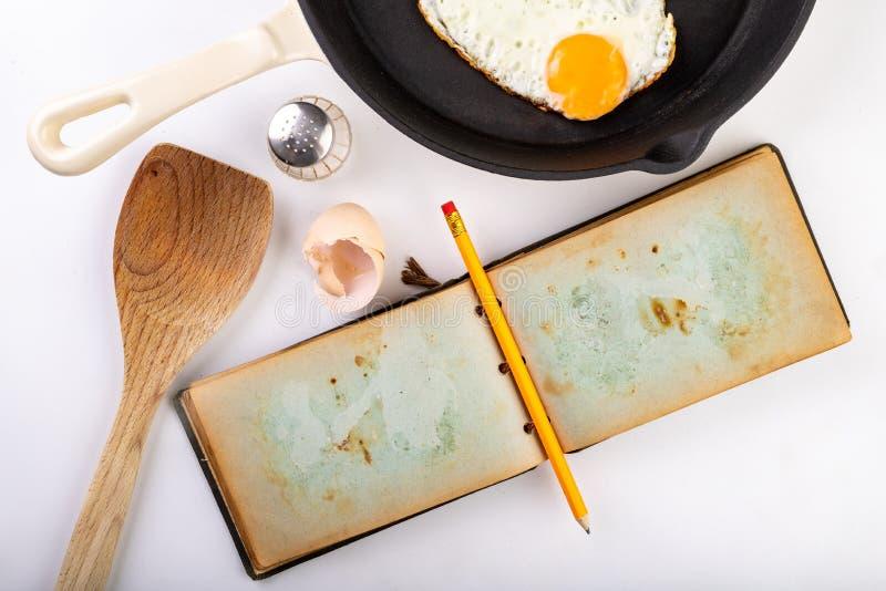 在一个生铁长柄浅锅的asty荷包蛋 准备根据食谱的一顿鲜美早餐从一个老笔记本 库存图片