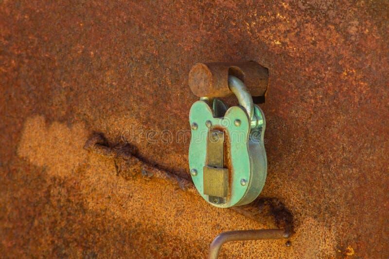 在一个生锈的老舱口盖的老蓝绿色挂锁 图库摄影
