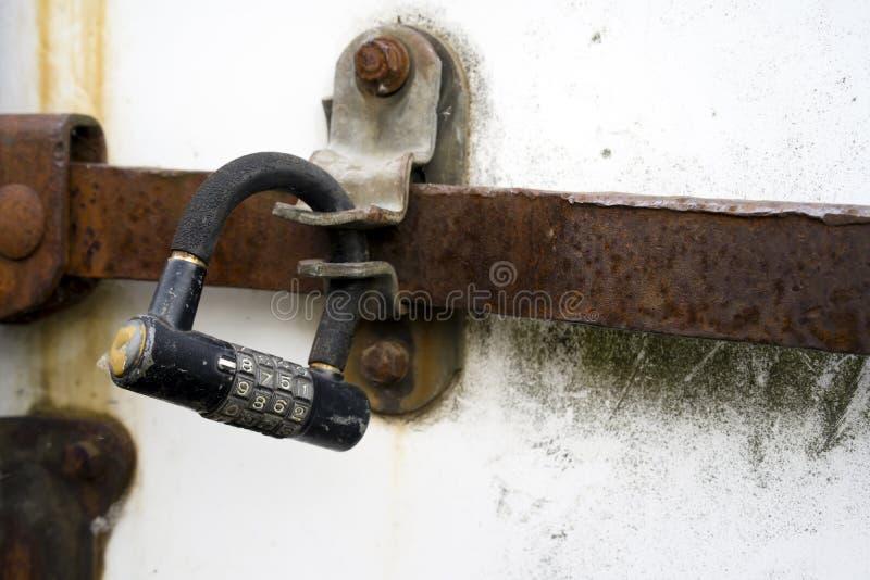 在一个生锈的闸式阀的老号码锁在老拖车门 免版税图库摄影