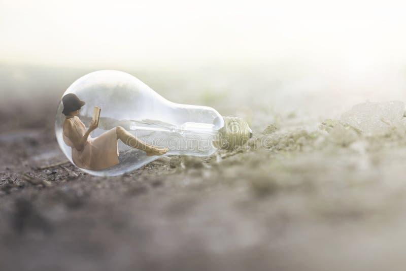 在一个电灯泡里面的小妇女读书 免版税图库摄影