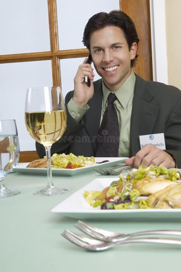 在一个电话的商人在餐桌上 图库摄影