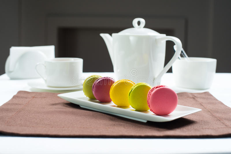 在一个白方块的五颜六色的蛋白杏仁饼干镀甜macarons和花 免版税图库摄影