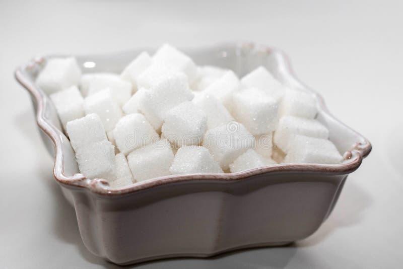 在一个白方块碗的糖立方体 免版税库存照片