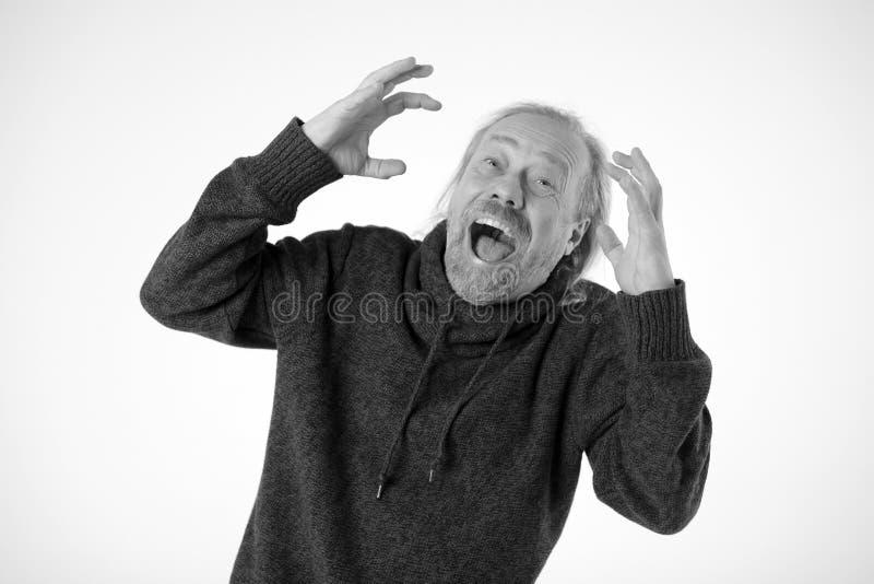 在一个白老人的面孔的鬼脸 手指被扭转 图库摄影