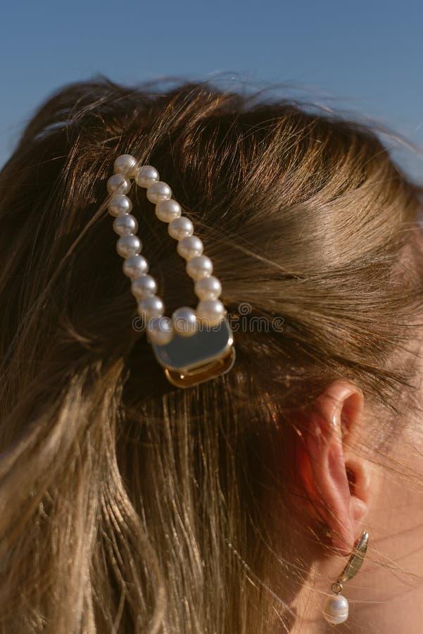 在一个白肤金发的女孩的头发的珍珠簪子 时髦的发夹 免版税库存图片