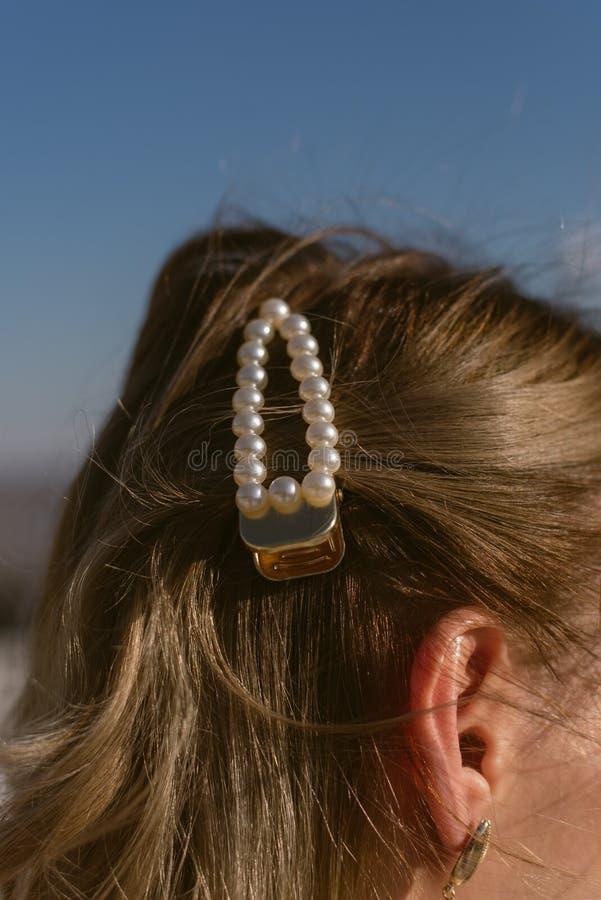 在一个白肤金发的女孩的头发的珍珠簪子 库存照片