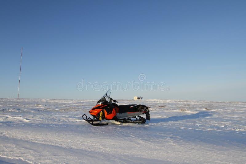 在一个白色冬天北极风景的一个红色雪机器与在地面上的雪蓝色不尽的天空 库存照片