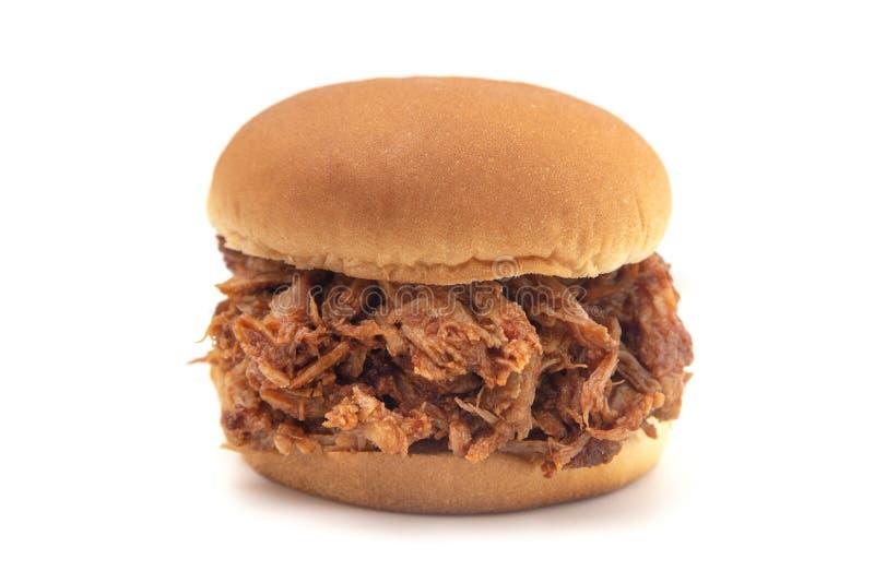 在一个白色小圆面包的被拉扯的猪肉三明治 免版税库存照片