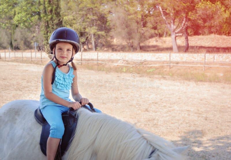 在一个白色小马的小女孩车手 免版税库存照片