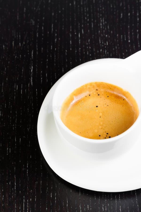 在一个白色杯子的伟大的意大利咖啡在黑木桌上 免版税库存照片