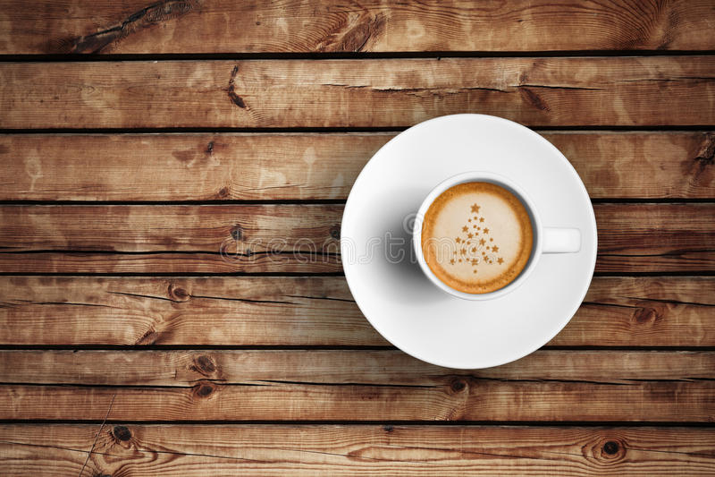 在一个白色杯子的伟大的意大利浓咖啡咖啡在与泡沫树圣诞节形状的木桌上 库存图片