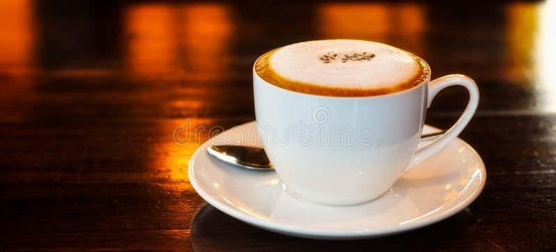 在一个白色杯子的咖啡在木桌上 库存照片