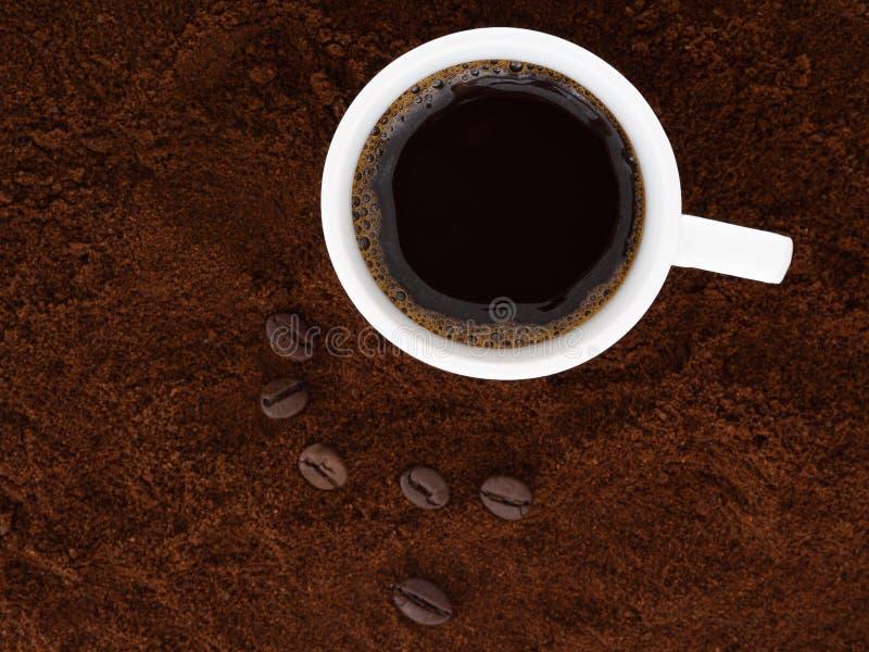 在一个白色杯子的强,黑色意大利浓咖啡,用新近地碾碎的咖啡和豆 免版税库存图片