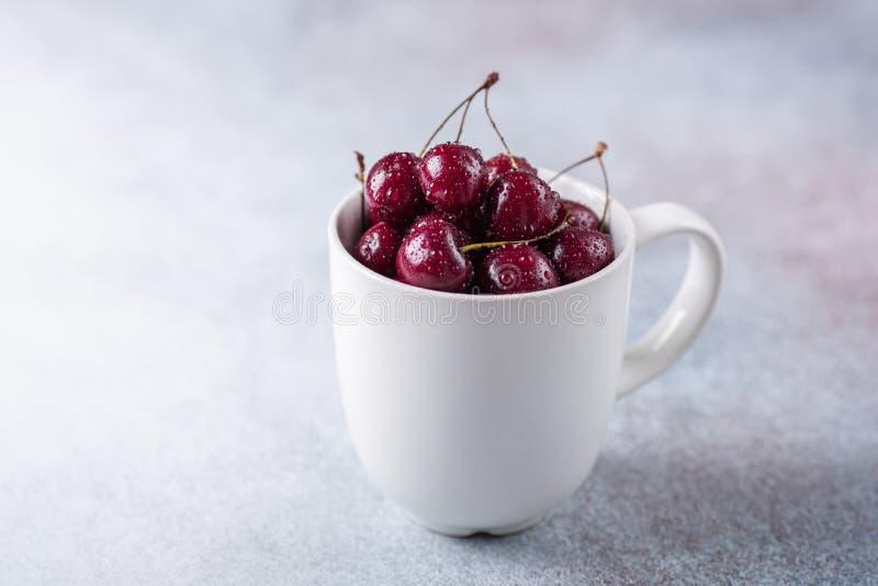 在一个白色杯子的新鲜的成熟红色樱桃在灰色石背景特写镜头水下落 库存图片