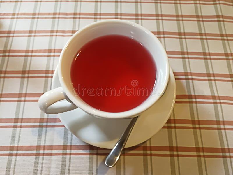 在一个白色杯子的果子茶在用一张方格的桌布盖的桌上 图库摄影