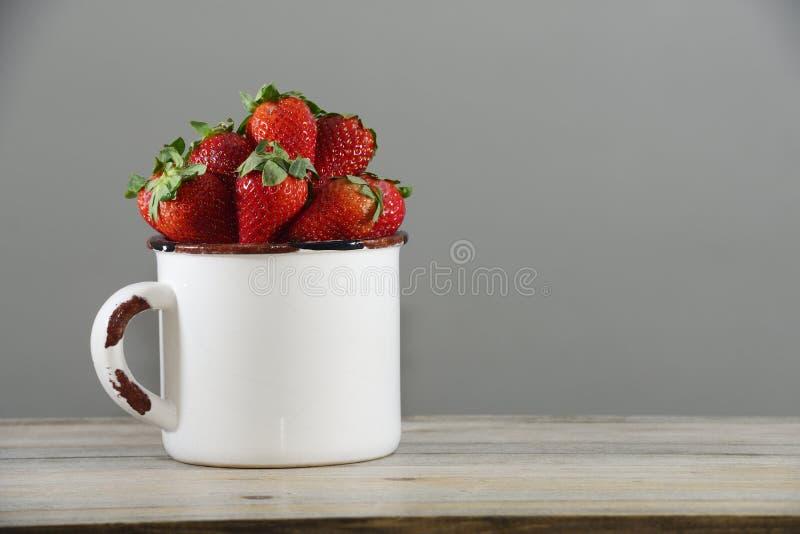 在一个白色杯子的草莓在一张木桌上 免版税库存照片