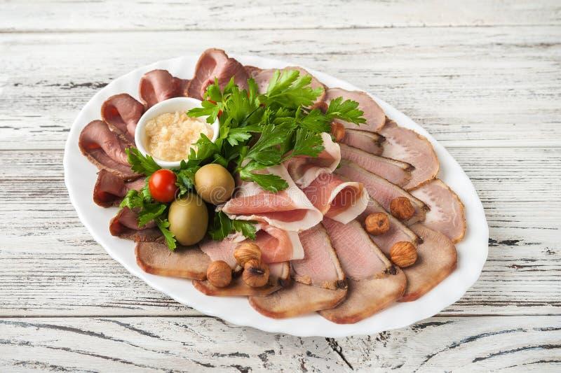 在一个白色板材特写镜头的肉盛肉盘 被烘烤的火腿,西班牙火腿,烤牛肉,熏制的鸭胸脯拷贝空间 库存图片