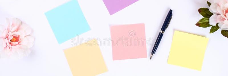 在一个白色桌面上的多彩多姿的稠粘的笔记贴纸在咖啡杯和键盘旁边 顶视图,平的布局 免版税图库摄影