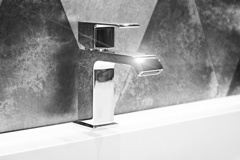 在一个白色水槽的豪华现代样式龙头搅拌器在一个美丽的灰色金属样式卫生间里 库存照片
