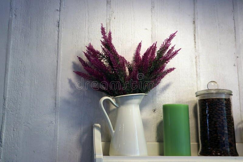 在一个白色水罐的花束海瑟在一个蜡烛和咖啡豆旁边的架子在一个玻璃瓶子 库存照片