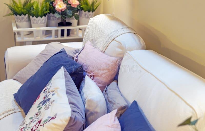 在一个白色沙发的装饰枕头在一个现代客厅内部 免版税图库摄影