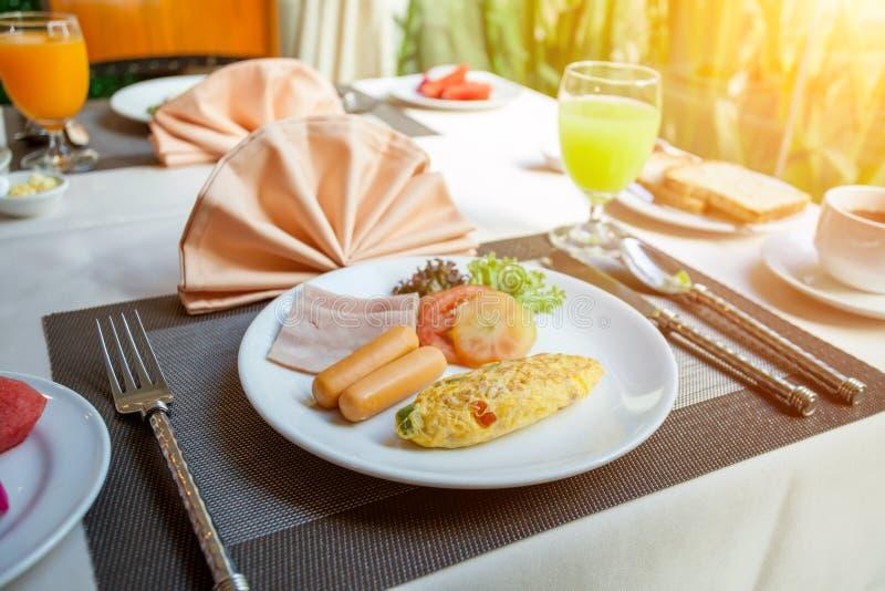 在一个白色盘的香肠火腿蕃茄煎蛋卷煎蛋在桌上早餐 免版税库存图片