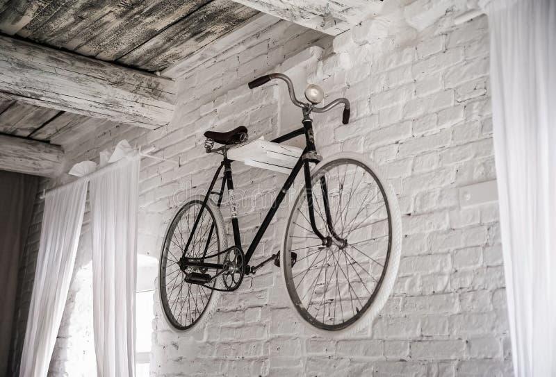 在一个白色石墙上的老白色自行车whist 库存照片
