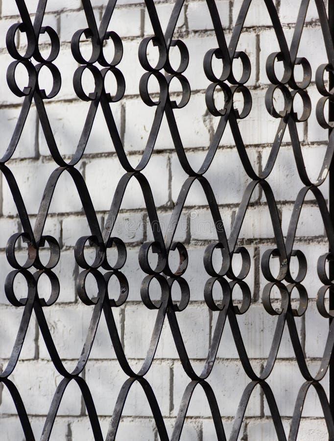 在一个白色砖墙上的伪造的钢金属装饰格栅 黑锻铁篱芭的片段 纹理元素或背景 免版税库存照片
