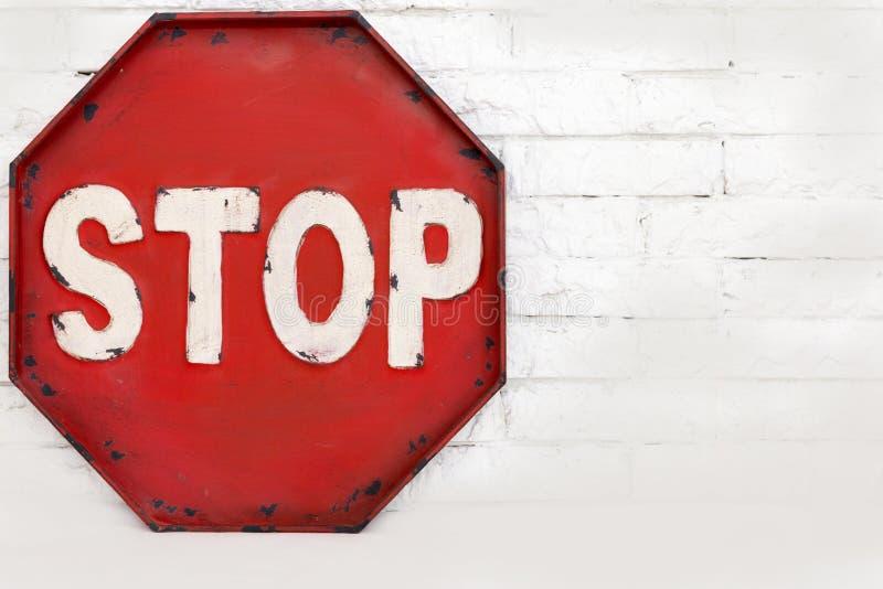 在一个白色砖墙上的红色中止标志,对象 免版税图库摄影