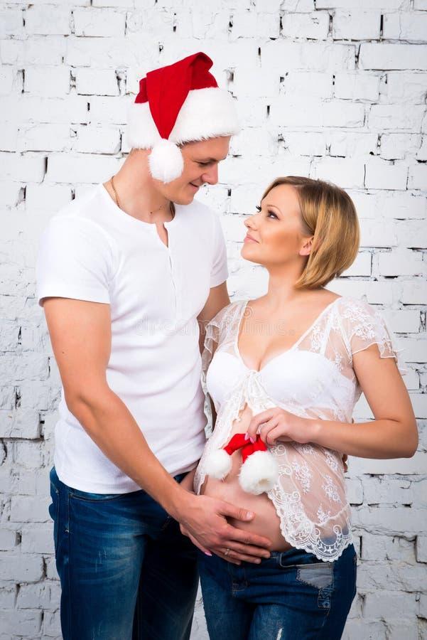 在一个白色砖墙附近的年轻人怀孕的夫妇有一个小儿童圣诞老人帽子的 免版税库存图片