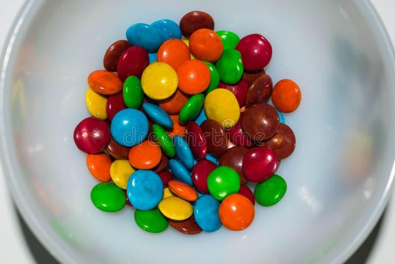 在一个白色碗的五颜六色的上漆的巧克力糖 免版税库存照片