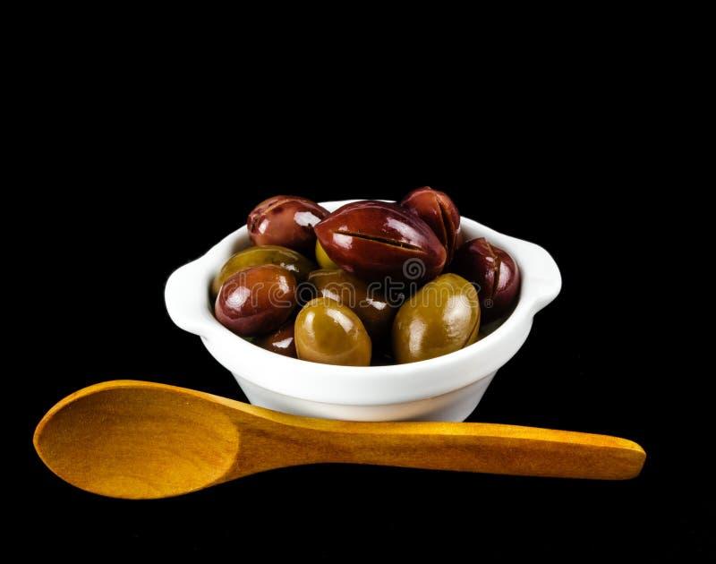在一个白色碗的桃红色橄榄在黑色 库存照片