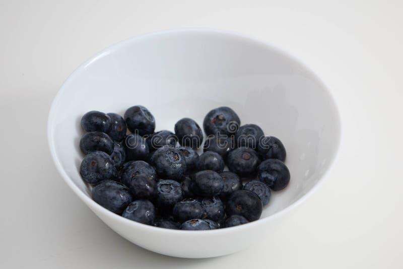 在一个白色碗的水多的黑莓,在一块白色板材的莓果在白色背景 免版税库存照片