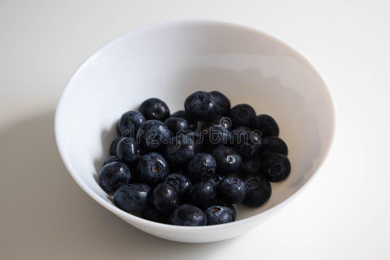 在一个白色碗的水多的黑莓,在一块白色板材的莓果在白色背景 库存图片