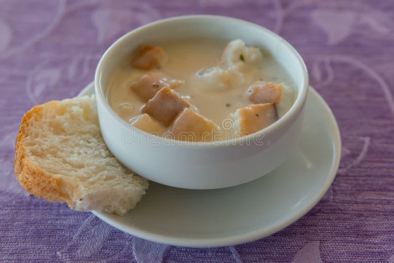 在一个白色碗的汤纯汁浓汤用在餐巾和背景织品的油煎方型小面包片 库存图片