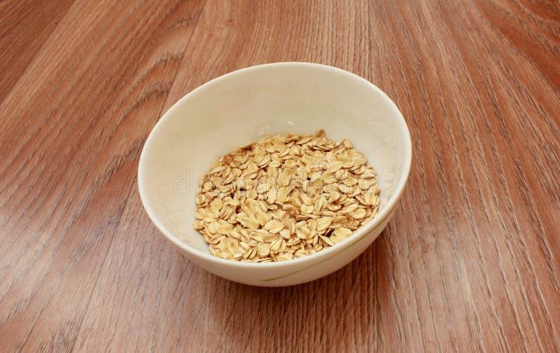 在一个白色碗的燕麦剥落在木头 免版税库存图片