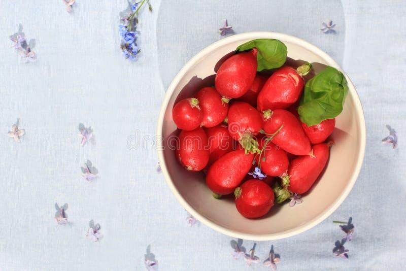在一个白色碗的红色萝卜在与淡紫色花的灰色织品背景 免版税库存图片