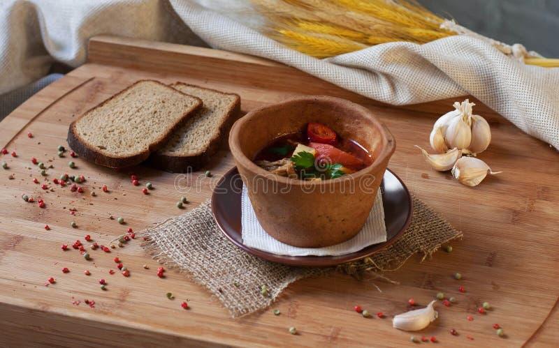 在一个白色碗的肉汤在木背景 免版税库存照片